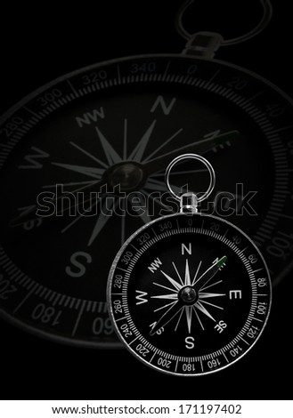 Classical compass, showing directions, with a bigger transparent one on black background - stock photo