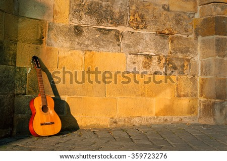 classical guitar in front of a church wall