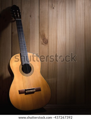 Classical guitar on wood background with copyspace.