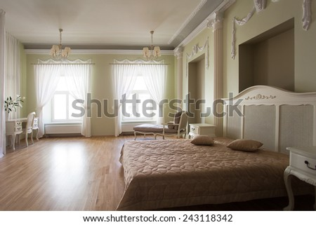 Classical interior of a bedroom with a bed, desk and couch at the window - stock photo
