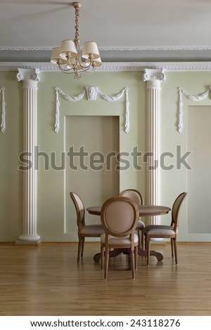 Classical interior with a round dining table and chairs - stock photo