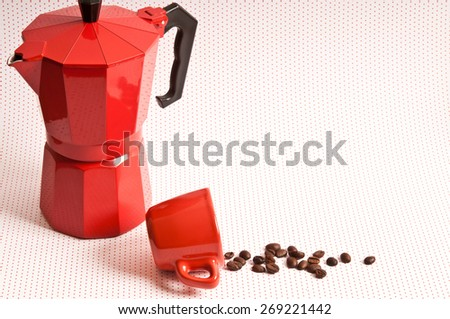 classical Italian coffee make and red cup fallen with coffee beans spilled out  - stock photo