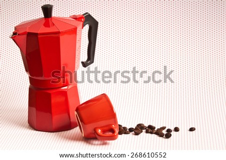 classical Italian coffee maker  pot and red cup fallen with coffee beans spilled out  - stock photo