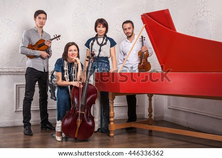 Classical music quartet posing after the concert with their instruments in hall, smiling and looking at camera at white background. Casual style. Studio shot.