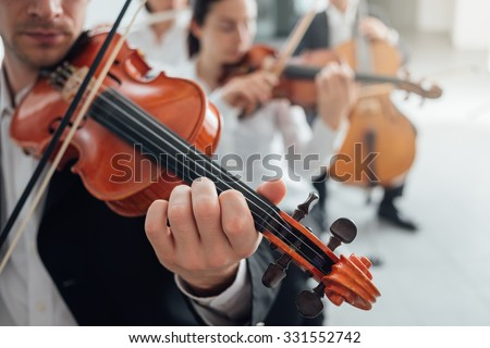 Classical music symphony orchestra string section performing, male violinist playing on foreground, music and teamwork concept - stock photo