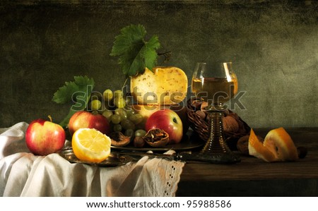 Classical still life with fruit, cheese, nuts and wine - stock photo