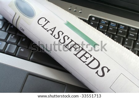 Classified ads section of the newspaper  laying on a laptop - stock photo