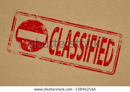 Classified rubber stamp symbol on brown paper background  - stock photo