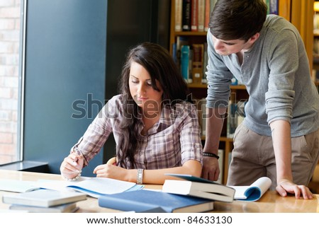 Classmates helping each other in a library - stock photo