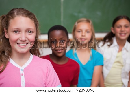 Classmates posing in a row in a classroom - stock photo