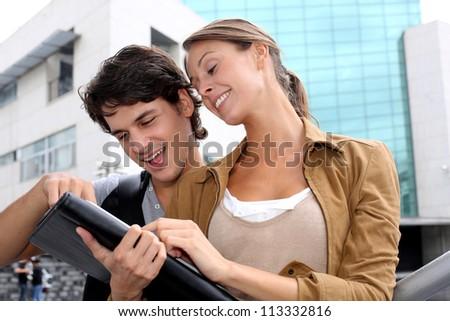 Classmates studying on digital tablet outside - stock photo
