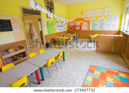 classromm of kindergarten with tables and small yellow chairs for children - stock photo