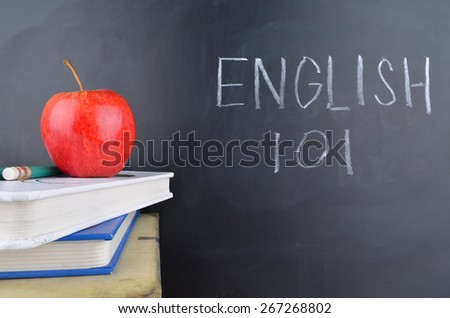 Classroom,apple,books and blackboard with handwriting in white chalk