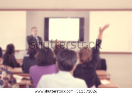 Classroom blur with instructor in front and raise up hand student - stock photo