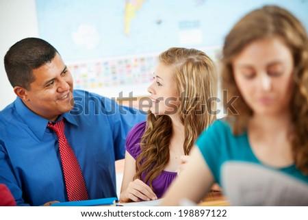 Classroom: Cheerful Teacher Helps Girl At Desk - stock photo