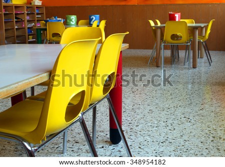 classroom of a nursery with the little yellow chairs and tables - stock photo