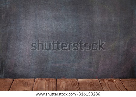 Classroom table in front of blackboard. View with copy space - stock photo