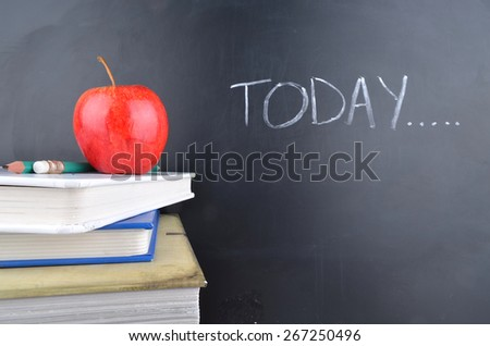 Classroom with apple, books and blackboard