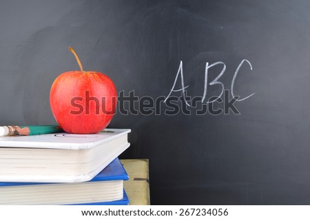Classroom with apple,books and blackboard with handwriting