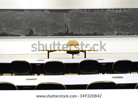classroom with black board, empty table and chair - stock photo