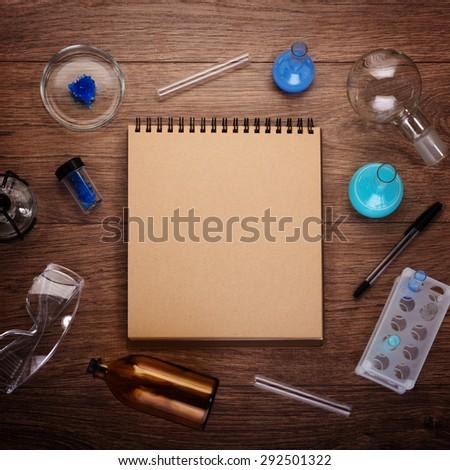 classroom with chemistry glassware and education notebook on the desk next to blackboard - stock photo