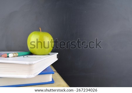 Classroom with green apple,books and blackboard - stock photo