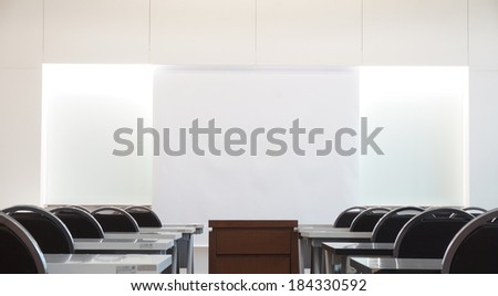 Classrooms on campus have a white background instead of a chalkboard, a desk, a chair and a table in the middle for placing overhead.                               - stock photo