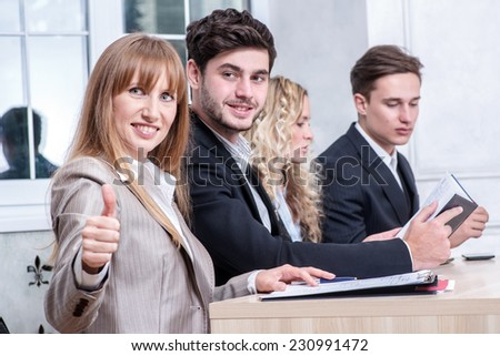Classy business. businessman or businesswoman sitting at a desk and showing thumb up while her colleagues businessmen talking in the background - stock photo
