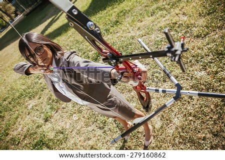 Classy Businesswoman Practicing Archery Outdoors - stock photo