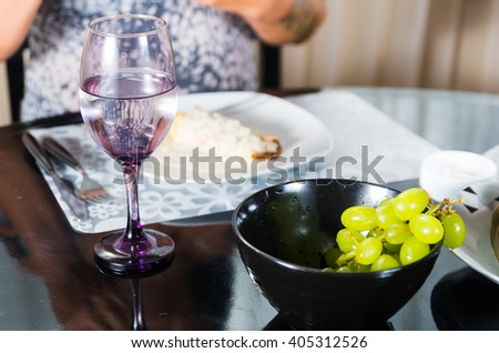 Classy dinner table setting with black bowl of green grapes in front focus