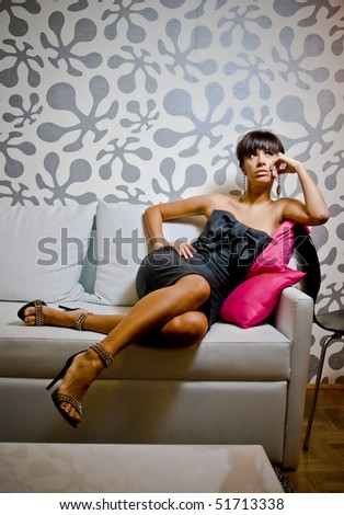 Classy girl sitting on the sofa - stock photo