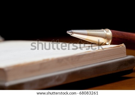 Classy pen lying on a notebook against a black background - stock photo