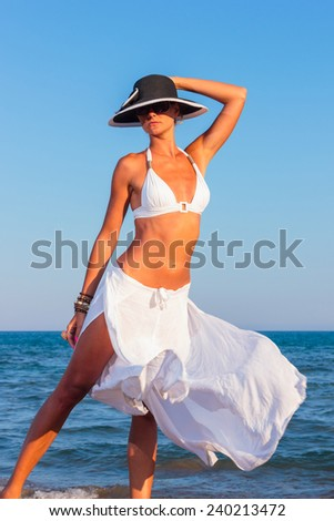 Classy young woman relaxing by the beach - stock photo