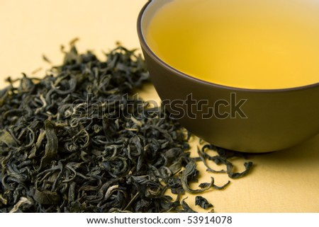 clay cup with green tea in dried tea leaves