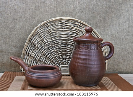 Clay jar and clay ladle standing on table  - stock photo