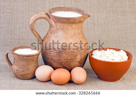 Clay jug and cup of milk, eggs and curds - stock photo