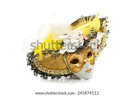 Clay mask with golden decoration and hat over white background - stock photo