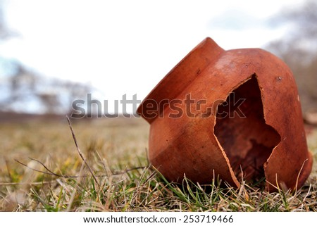 Clay pot in a field - stock photo