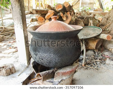 Clay Pot with Boiled Water on Fire Stove, Thailand. (2) - stock photo