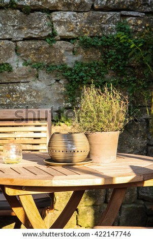 Clay pot with herbs on wooden table, stone wall background - stock photo