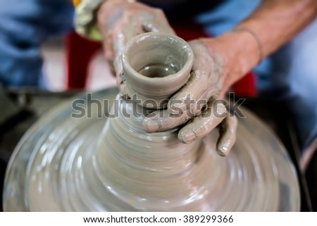 Clay potter creating on the pottery wheel - stock photo