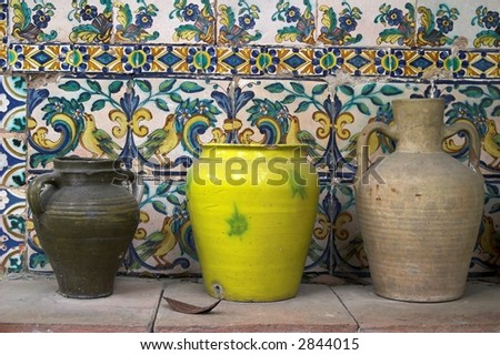 clay vases in front of old decorative tiled wall - stock photo