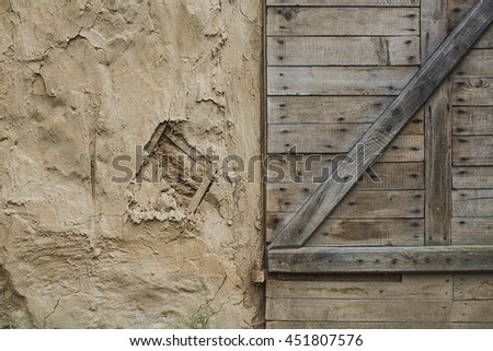 clay wall and old wooden door - stock photo