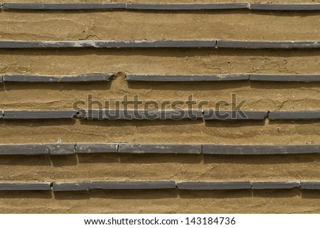 Clay Wall with Tiles worked in - stock photo