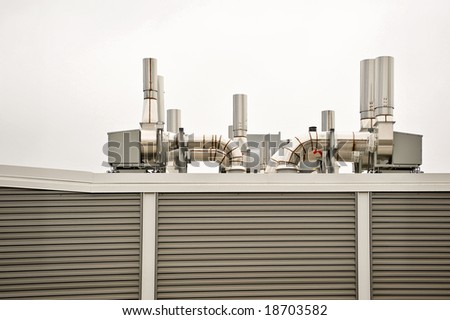 Clean air handling equipment on top of a building with striped panel sides. - stock photo