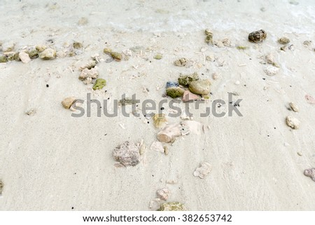 Clean and clear water with small reflections and smooth stones & leaf beneath - stock photo