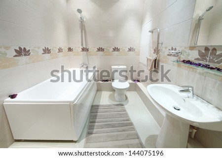 Clean and new bathroom with toilet with tiles on walls in new apartment. - stock photo