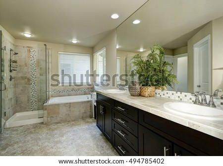 Clean and tidy bathroom interior. Long modern vanity cabinet with two sinks, bathtub with tile trim and shower. Northwest, USA