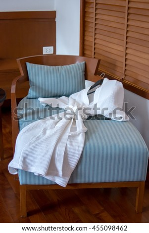 clean bathrobe on sofa bed in upscale hotel. white bathrobe on the bed prepare to use in pool villa hotel. Image with shadow - stock photo