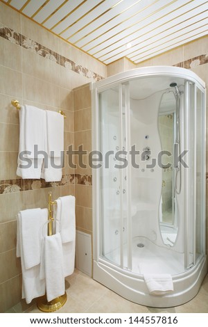 Clean bathroom with shower cabin and hangers with white towels. - stock photo